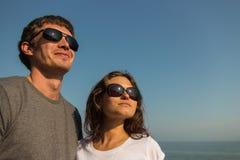 Schöne junge Paare, die zusammen in Richtung der Sonne blicken Stockfoto