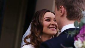 Schöne junge Paare gerade eingeführt von der Kirche, in der sie offiziell Frau und Ehemann standen und versprachen zu sein stock video footage
