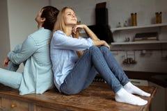 Schöne junge Paare im zufälligen Stoff, der auf dem Tisch sitzt stockfoto