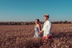 Schöne junge Paare, Mann und Frau, gehendes Weizenfeld im Sommer, jeder des anderen Hand halten, Lächeln glücklich romantisch lizenzfreies stockbild