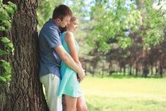 Schöne junge Paare zusammen, Mann, der verliebte Frau am Sommerpark umarmt stockfotografie