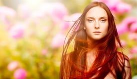 Schöne junge rote Frau über Herbsthintergrund Lizenzfreie Stockbilder
