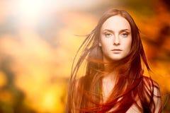 Schöne junge rote Frau über Herbsthintergrund Lizenzfreie Stockfotografie