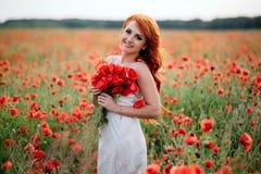 Schöne junge rothaarige Frau auf dem Mohnblumengebiet, das einen Blumenstrauß von Mohnblumen hält lizenzfreie stockfotos