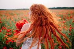 Schöne junge rothaarige Frau auf dem Mohnblumengebiet mit dem Fliegenhaar lizenzfreie stockfotos
