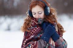 Schöne junge rothaarige Frau in den blauen Kopfhörern und in den Handschuhen Stockbilder