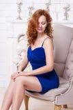 Schöne junge rothaarige Frau in einem blauen Kleid Stockbilder