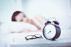 Schöne junge schlafende Frau beim im Bett auf dem Hintergrund des Weckers bequem und himmlisch liegen lizenzfreie stockfotografie