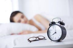 Schöne junge schlafende Frau beim im Bett auf dem Hintergrund des Weckers bequem und himmlisch liegen stockfotos