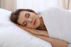 Schöne junge schlafende Frau beim im Bett bequem und himmlisch liegen Früher Morgen, wachen Sie für Arbeit oder auf stockfoto