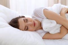 Schöne junge schlafende Frau beim im Bett bequem und himmlisch liegen Früher Morgen, wachen Sie für Arbeit oder auf stockfotografie