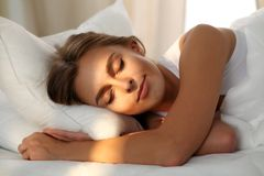 Schöne junge schlafende Frau beim im Bett bequem und himmlisch liegen Sonnenstrahldämmerung auf ihrem Gesicht stockfotografie