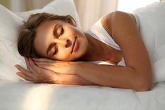 Schöne junge schlafende Frau beim im Bett bequem und himmlisch liegen Sonnenstrahldämmerung auf ihrem Gesicht lizenzfreies stockbild