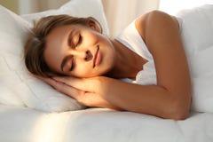 Schöne junge schlafende Frau beim im Bett bequem und himmlisch liegen Sonnenstrahldämmerung auf ihrem Gesicht Stockbilder