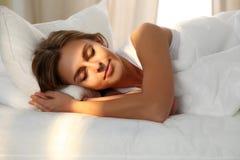 Schöne junge schlafende Frau beim im Bett bequem und himmlisch liegen Sonnenstrahldämmerung auf ihrem Gesicht lizenzfreie stockbilder