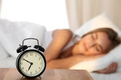Schöne junge schlafende und beim im Bett auf dem Hintergrund der Warnung bequem und himmlisch liegen lächelnde Frau stockbild