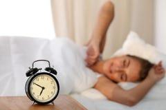 Schöne junge schlafende und beim im Bett auf dem Hintergrund der Warnung bequem und himmlisch liegen lächelnde Frau stockbilder