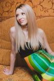 Schöne junge schwangere Frau, die auf Couch sitzt Stockbild