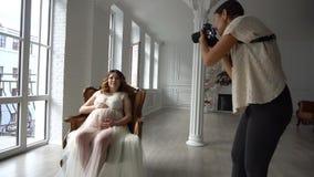 Schöne junge schwangere Frau, die auf Stuhl im weißen peignoir sitzt und zum Fotografen aufwirft stock video footage