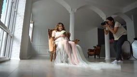 Schöne junge schwangere Frau, die auf Stuhl im weißen peignoir sitzt und zum Fotografen aufwirft stock footage