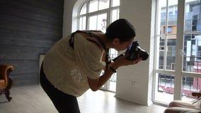 Schöne junge schwangere Frau, die auf Stuhl im weißen peignoir sitzt und zum Fotografen aufwirft stock video