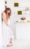 Schöne junge schwangere Frau im gekräuselten Sommer kleiden zu Hause an stockbild