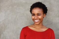 Schöne junge schwarze Frau, die Auge und das Lächeln blinzelt Lizenzfreie Stockbilder