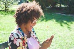 Schöne junge schwarze Frau, die den Smartphone auf den Park lacht und betrachtet lizenzfreie stockbilder