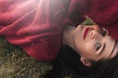 Schöne junge sexy brunette Frau, die gestrickte Strickjacke und die Kamera, liegend auf dem Gras betrachtend lächelt, trägt stockbild