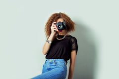 Schöne junge Frau in den Jeans mit einer Kamera in den Händen des gelockten Haares im Studio Stockbilder