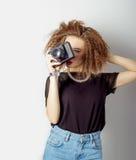 Schöne junge Frau in den Jeans mit einer Kamera in den Händen des gelockten Haares im Studio Lizenzfreie Stockfotos