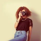 Schöne junge Frau in den Jeans mit einer Kamera in den Händen des gelockten Haares im Studio, Retro- Filter Lizenzfreie Stockfotos