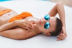 Schöne junge sexy Frau, die in Bikini während des sunbath nahe bei Swimmingpool legt stockbilder