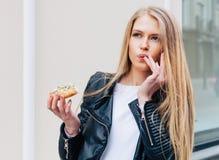 Schöne junge Frau, die einen Donut, ihre Finger leckend isst, die Vergnügen eine europäische Stadtstraße nehmen outdoor Warm Stockfotos