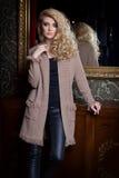 Schöne junge sexy Frau mit dem langen blonden Haar, helles Make-up Smokey Eyes, der eine Strickjacke nahe bei einem Aufbereiter u Lizenzfreie Stockfotografie