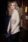 Schöne junge sexy Frau mit dem langen blonden Haar, helles Make-up Smokey Eyes, der eine Strickjacke nahe bei einem Aufbereiter u Lizenzfreie Stockfotos
