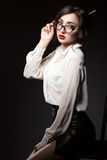 Schöne junge sexy Geschäftsfrau mit dunklem updo Haar, das über ihren modischen Gläsern im modernen Rahmen direkt schaut lizenzfreies stockfoto