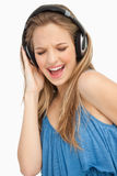 Schöne junge singende Frau beim Hören zu m Stockbilder