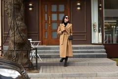 Schöne junge stilvolle brunette Frau, die den langen beige Mantel, schwarzes Hemd und die Schuhe, gehend entlang die Stadtstraßen stockbilder