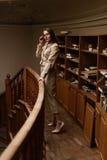 Schöne junge stilvolle Dame, die auf Balkon in der Weinlesebibliothek steht lizenzfreies stockbild