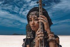 Schöne junge stilvolle Stammes- Frau im orientalischen Kostüm, das draußen Sitar spielt Abschluss oben lizenzfreies stockbild