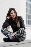 Schöne junge Studentin in der Jacke, die sich draußen auf einer alten Steinwand hinsetzt und während des Herbstfrühlingstages läc Lizenzfreies Stockfoto