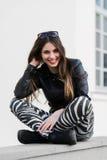 Schöne junge Studentin in der Jacke, die sich draußen auf einer alten Steinwand hinsetzt und während des Herbstfrühlingstages läc Stockfotos