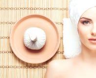 Schöne, junge und gesunde Frau im Badekurortsalon auf Bambusmatte S Lizenzfreie Stockfotografie