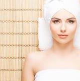Schöne, junge und gesunde Frau im Badekurortsalon auf Bambusmatte S Lizenzfreie Stockbilder