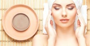 Schöne, junge und gesunde Frau im Badekurortsalon auf Bambusmatte S Stockbild