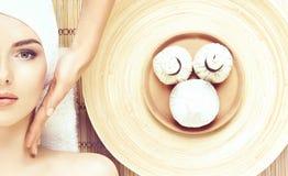 Schöne, junge und gesunde Frau im Badekurortsalon auf Bambusmatte S Stockfotografie