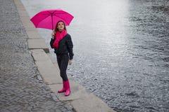 Schöne junge und glückliche blonde Frau in einem hellen rosa Schal, in Gummistiefeln und in einem Regenschirm gehend in eine regn Lizenzfreie Stockbilder