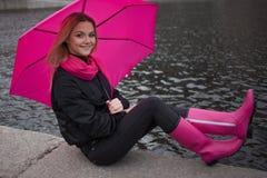 Schöne junge und glückliche blonde Frau mit buntem Regenschirm auf der Straße Das Konzept der Bestimmtheit und des Optimismus Lizenzfreie Stockfotos