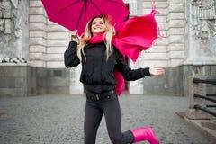 Schöne junge und glückliche blonde Frau mit buntem Regenschirm auf der Straße Das Konzept der Bestimmtheit und des Optimismus Lizenzfreies Stockfoto